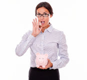 告诉拿着桃红色存钱罐的女实业家 库存照片