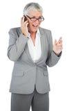 告诉激动的女实业家某人有她的手机的 免版税图库摄影