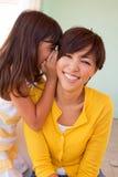 告诉的母亲和的女儿微笑和秘密 库存照片
