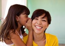 告诉的母亲和的女儿微笑和秘密 免版税库存图片