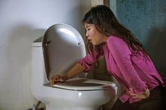 呕吐和投掷在洗手间WC的年轻醉酒或怀孕的亚裔妇女感觉不适和病态的遭受的肚子疼和 图库摄影