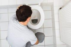 呕吐在卫生间里的人 库存图片