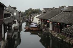 周庄,中国:老房子和小船反射在村庄运河 免版税库存图片