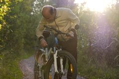 周期乘驾的老人在乡下 免版税库存照片