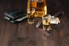 周末在桌、玻璃用白兰地酒和金钱上喝在tabl 库存照片