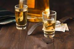 周末在桌、玻璃用白兰地酒和金钱上喝在tabl 库存图片