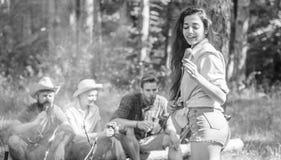 周末高涨 与朋友的野餐在篝火附近的森林里 有的公司远足野餐自然背景 游人与 免版税库存照片