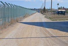 周界栅栏和泥铺跑道 免版税库存图片
