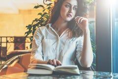 周道地坐在咖啡馆的妇女在与一个法院记录、地址本、学报和神色的桌上窗口 免版税库存图片