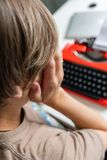 周道地工作在她的书桌红色打字机的一本书的妇女作家 图库摄影