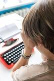 周道地工作在她的书桌红色打字机的一本书的妇女作家 免版税库存图片