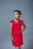 周道地看入的红色礼服的青少年的女孩 免版税库存照片