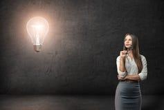 戴周道地看在发光的电灯泡的眼镜的年轻女实业家 免版税库存照片