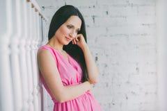 周道地看的女孩下来 在桃红色礼服的美好的妇女模型对一个白色砖墙 库存照片