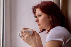 周道地看窗口的中年妇女,举行在手白色杯子茶或咖啡 从工作或差事的休息 库存照片
