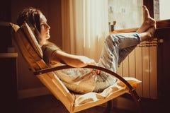 周道的概念 关闭在想法失去的画象哀伤的妇女lounging在舒适的现代椅子在窗口附近 温暖的自然lig 免版税库存图片
