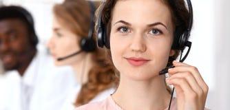 呼叫中心运算符 耳机的年轻美丽的深色的妇女 到达天空的企业概念金黄回归键所有权 免版税图库摄影