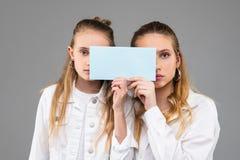 呼吁运载清楚的标识牌的白色成套装备的悦目相似的女孩 免版税图库摄影