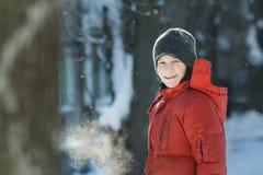 呼吸与可看见的蒸汽嘴的快乐的十几岁的男孩首肩冬天室外画象在冷淡的晴天 图库摄影
