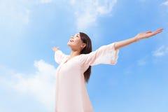 呼吸与被举的胳膊的妇女新鲜空气 免版税图库摄影