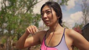 呼吸和变冷静在坚硬连续锻炼以后的年轻美丽的疲乏和满身是汗的赛跑者亚裔妇女在足迹r 影视素材