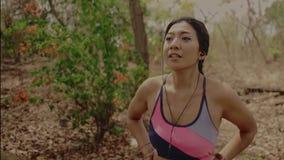 呼吸和变冷静在坚硬连续锻炼以后的年轻美丽的疲乏和满身是汗的赛跑者亚裔妇女在足迹r 股票录像