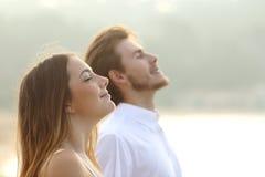 呼吸深新鲜空气的男人和妇女夫妇  图库摄影