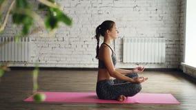 呼吸瑜伽学生的侧视图放松和,当坐在明亮的席子时的莲花坐 可爱的妇女是 影视素材