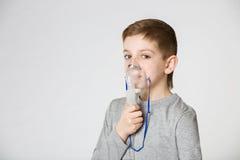 呼吸通过吸入面具的男孩 免版税库存照片