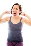 呼喊与在她的耳朵的手指的少妇 免版税库存照片