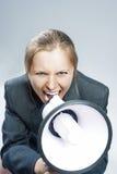 呼喊使用扩音机的白种人白肤金发的妇女 反对灰色Bac 库存图片