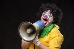 呼喊入在黑背景的一台扩音机的可怕小丑 库存照片