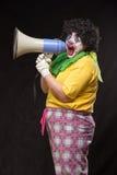 呼喊入在黑背景的一台扩音机的可怕小丑 免版税库存图片