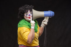 呼喊入在黑背景的一台扩音机的可怕小丑 免版税库存照片