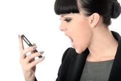 呼喊入手机的恼怒的沮丧的懊恼妇女 免版税库存照片