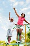 呼喊和举手的非洲孩子在公园 免版税库存图片