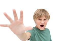 呼喊和做停车牌用手的愤怒的小男孩 库存照片
