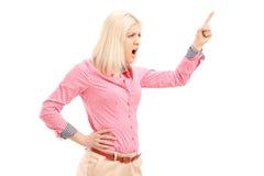 呼喊和指向与手指的猛烈少妇 免版税库存照片