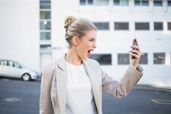 呼喊在她的电话的恼怒的时髦的女实业家 免版税库存照片