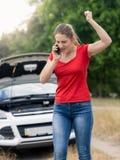 呼喊在手机的恼怒的妇女由于残破的汽车o 免版税库存图片