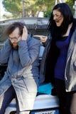 呼喊在打破的丈夫的恼怒的妇女汽车 免版税库存照片