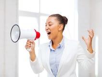 呼喊在扩音机的严密的女实业家 免版税库存照片