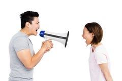 呼喊在扩音机的少妇的恼怒的人 免版税图库摄影