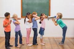 呼喊在教室的逗人喜爱的学生 免版税库存图片