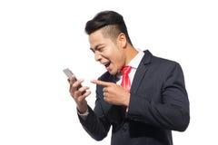 呼喊在智能手机的恼怒的商人,站立在白色ba 免版税库存照片
