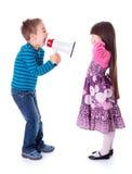 呼喊在有扩音机的女孩的男孩 免版税库存照片