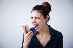 呼喊在灰色背景的电话的恼怒的妇女 免版税图库摄影