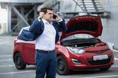 呼喊在电话的恼怒的商人由于残破的新的汽车 库存照片