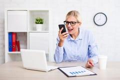 呼喊在电话的恼怒的女商人在办公室 免版税图库摄影