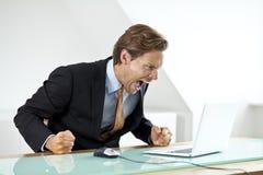 呼喊在膝上型计算机的沮丧的商人 库存图片